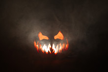 Scary Halloween Jack O Lantern Face Glowing In Smoke.