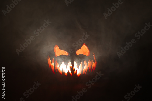 Fotomural  Scary Halloween jack o lantern face glowing in smoke.