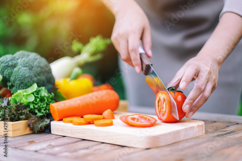 Canvas Closeup image of a woman cutting and chopping tomato by knife on wooden board
