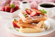 Leinwandbild Motiv Belgian waffles with strawberry and powdered sugar on white plate, pink background