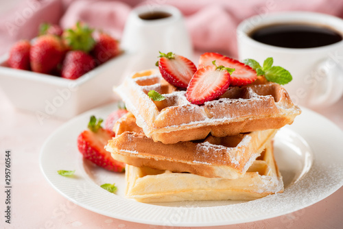 Fotografía  Belgian waffles with strawberry and powdered sugar on white plate, pink backgrou