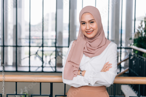 Foto Young happy and successful South East Asian Islamic business woman with arms cro