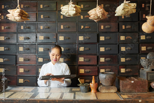 Papiers peints Pharmacie Traditional Chinese medicine practitioner using abacus for counting ingredients in her store