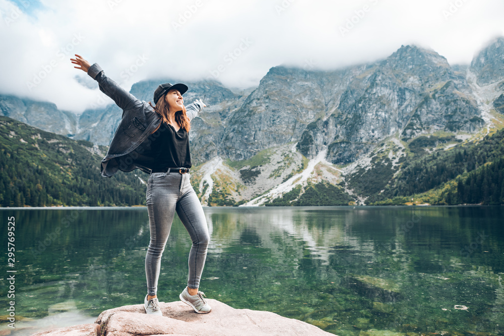 Fototapeta happy woman hands up looking at lake in mountains