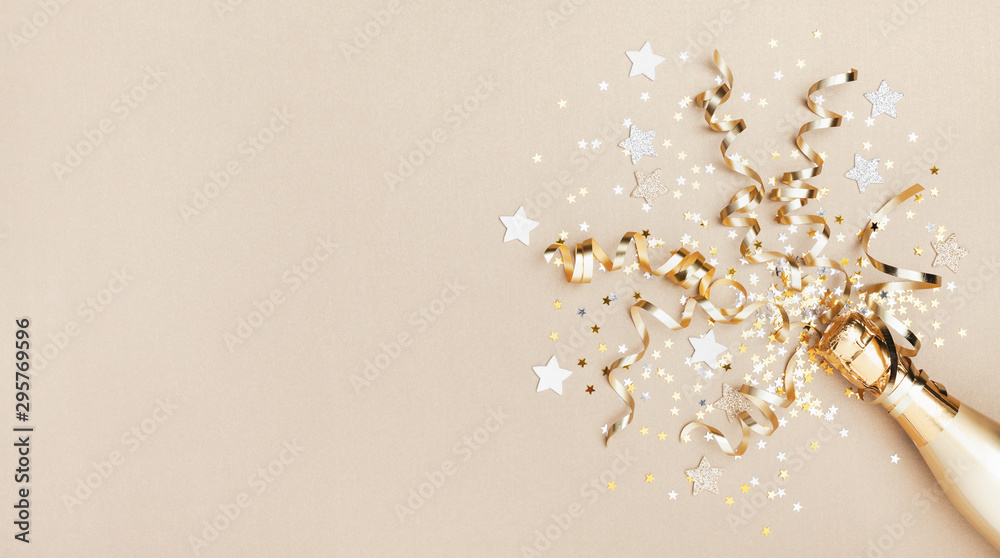 Fototapeta Celebration background with golden champagne bottle, confetti stars and party streamers. Christmas, birthday or wedding concept. Flat lay.