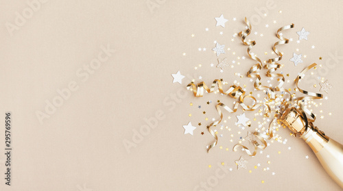 Fototapeta Celebration background with golden champagne bottle, confetti stars and party streamers. Christmas, birthday or wedding concept. Flat lay. obraz