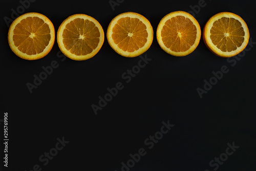border of sliced citrus fruit, citrus rounds in a line on black chalkboard background, sliced oranges, lemons, and limes, copy space, copyspace