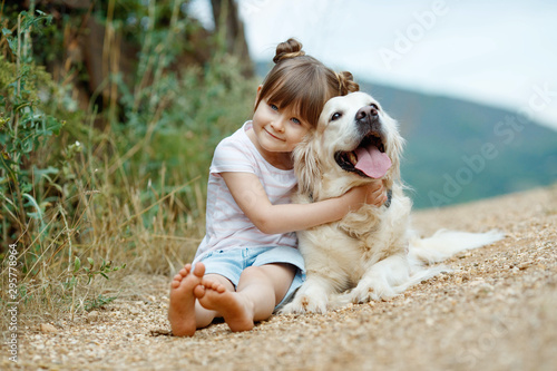 Obraz A child with a dog. Little girl plays with a dog in nature.  - fototapety do salonu