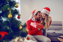 Overjoyed Handsome Bearded Man Sitting On Sofa In Living Room, Holding Gift And Hugging With His Girlfriend. Both Having Santa Hats On Heads. In Foreground Is Christmas Tree. Living Room Interior.