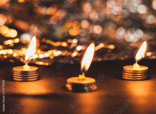 Three burning candles on pile of coins and bokeh in ht ebackground in Deepawali Canvas Print