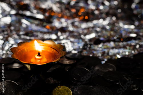 Top view of a glowing metal-lamp on a pile of coins and reflective background Wallpaper Mural