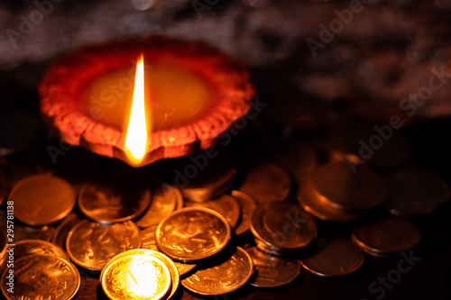 Top View of an earthen lamp glowing in the dark with money in the foreground for Wallpaper Mural