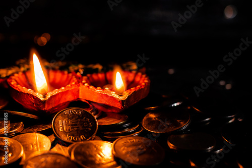 two glowing earthen lamps with lot of coins against a dark background - Diwali c Canvas Print