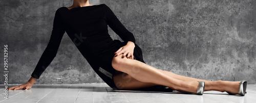 Pinturas sobre lienzo  Woman lying on a floor with long gorgeous legs on dark in black little dress