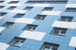 canvas print picture - White and blue apartment building facade ground view.