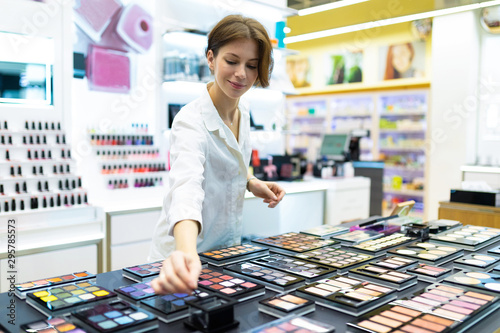 Obraz na plátne Young smiling woman in cosmetics shop is testing eye-shadows