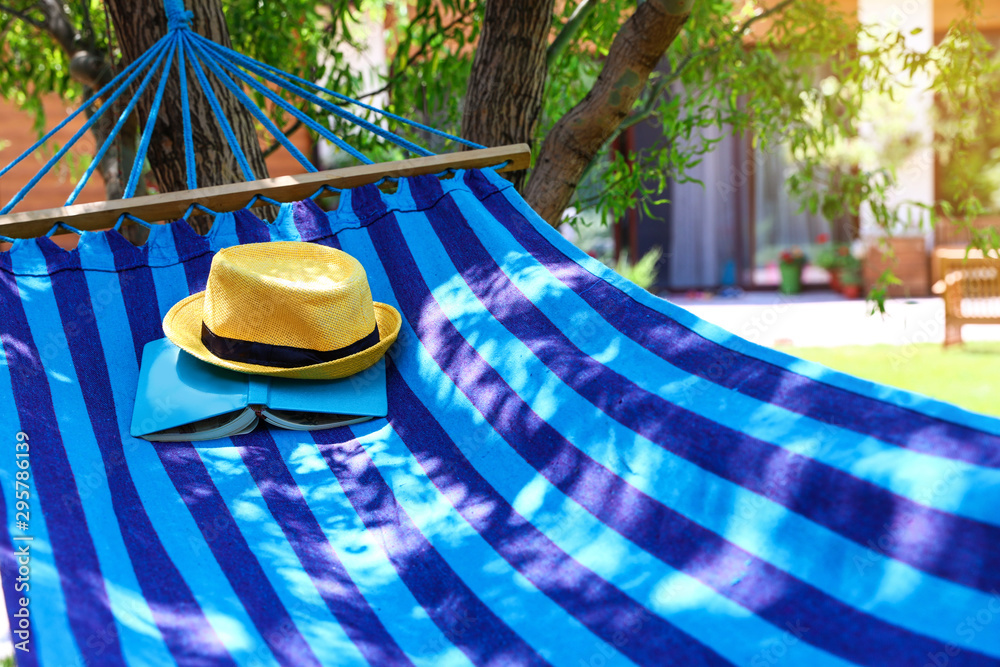 Fototapety, obrazy: Comfortable blue hammock with hat and book outdoors on sunny day