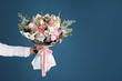 canvas print picture - Man holding beautiful flower bouquet on blue background, closeup view. Space for text