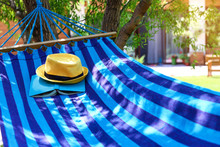 Comfortable Blue Hammock With Hat And Book Outdoors On Sunny Day
