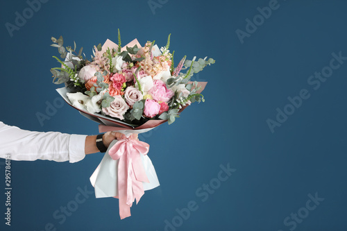 Canvas Print Man holding beautiful flower bouquet on blue background, closeup view