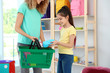 Little girl with mother choosing school stationery in shop