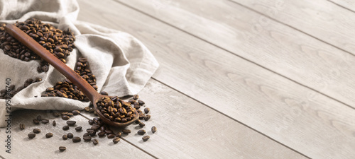 Fotografía  Fresh roasted coffee beans with spoon and burlap sack on a wooden surface, in pa