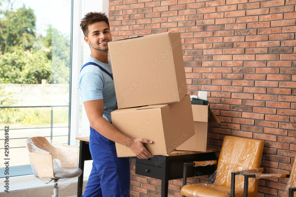 Fototapety, obrazy: Young worker carrying cardboard boxes in office. Moving service