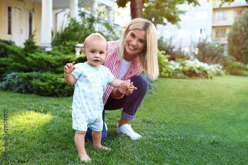 Nanny with cute little baby on green grass outdoors