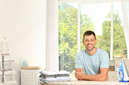 Handsome man with iron and clean laundry near board at home, space for text