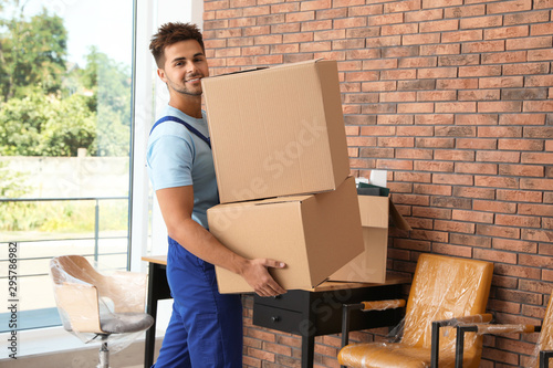 Young worker carrying cardboard boxes in office. Moving service - 295786982