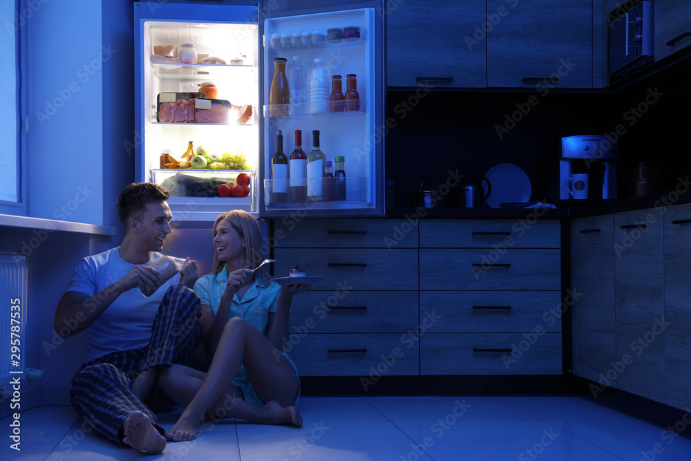 Fototapety, obrazy: Happy couple eating near refrigerator in kitchen at night