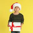 Leinwandbild Motiv Cute little boy in Santa hat with Christmas gift on yellow background