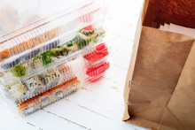 Stack Of Plastic Boxes With Sushi Roll Sets And Paper Bag. Food Delivery
