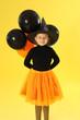 Leinwandbild Motiv Cute little girl with balloons wearing Halloween costume on yellow background