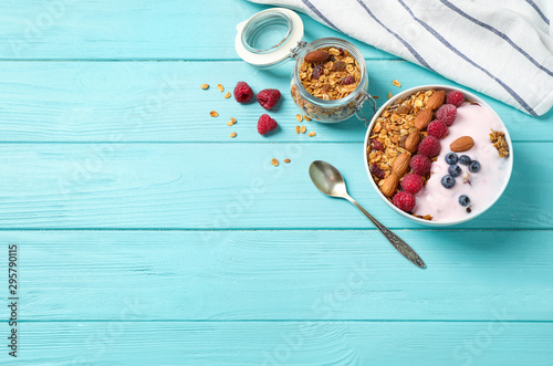 obraz lub plakat Tasty homemade granola served on blue wooden table, flat lay with space for text. Healthy breakfast
