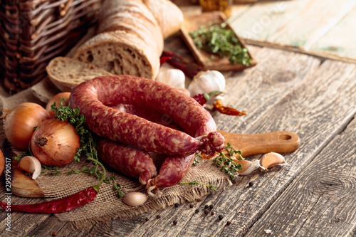 Dry-cured sausage with bread and spices on a old wooden table. Fototapet