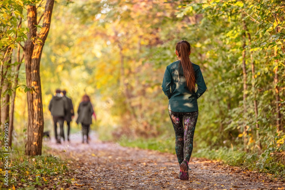 Fototapeta Woman walking in autumn forest nature path walk on trail woods background. Happy girl relaxing on active outdoor activity.