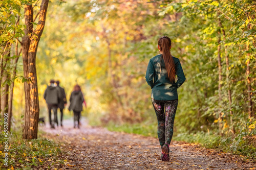 Obraz Woman walking in autumn forest nature path walk on trail woods background. Happy girl relaxing on active outdoor activity. - fototapety do salonu