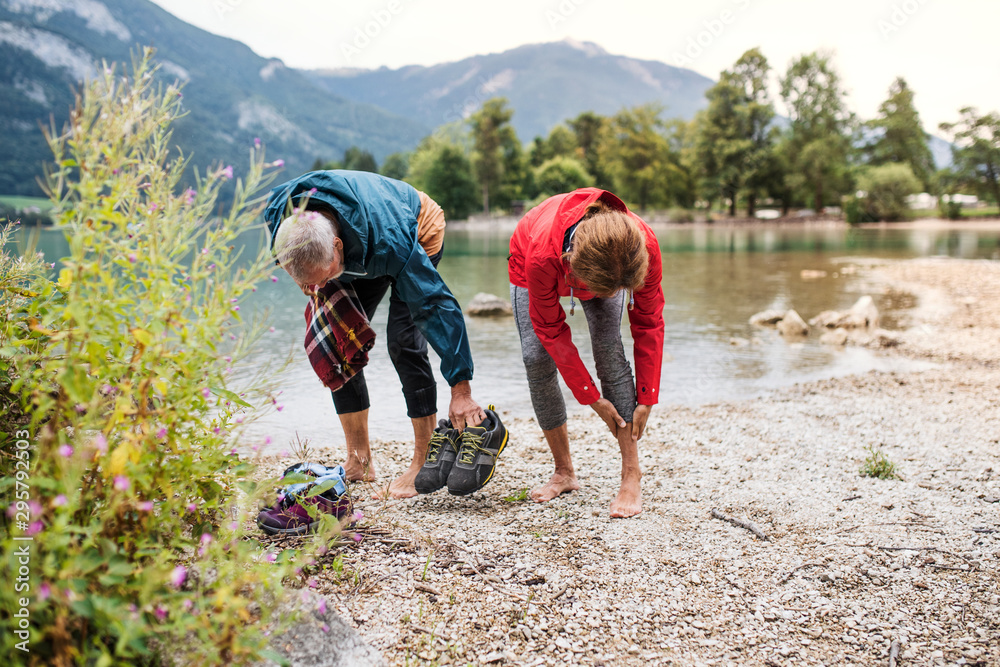 Fototapety, obrazy: A senior pensioner couple hikers standing by lake in nature, taking shoes off.