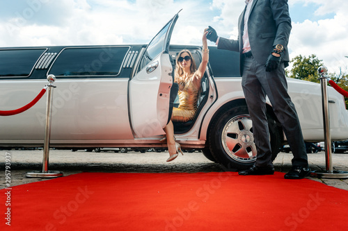 Driver helping VIP woman or star out of limo on red carpet Tableau sur Toile