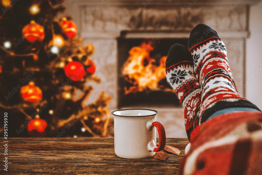 Fototapeta Woman legs with christmas socks and fireplace in home interiro