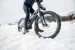 Leinwandbild Motiv Midsection of mountain biker riding in snow outdoors in winter.