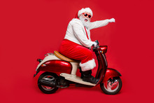 Profile Side View Portrait Of Nice Bearded Cheerful Funny Funky Purposeful Santa Claus Riding Moped Hurry Up Shopping Season North Pole Isolated On Bright Vivid Shine Vibrant Red Color Background