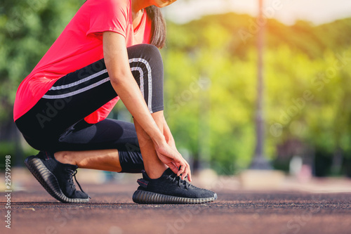 Crop image of woman runner lace her shoes and prepare to jogging with warm light Obraz na płótnie