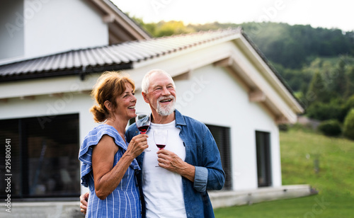 Foto  Portrait of senior couple with wine outdoors in backyard.