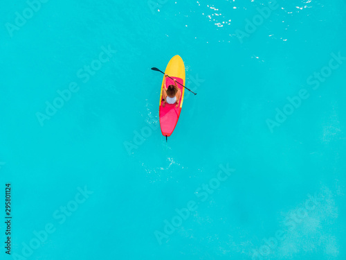 Poster Turquoise Attractive woman on stand up paddle board on a quiet blue ocean. Sup surfing in sea