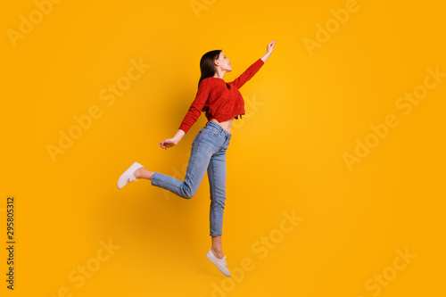 Obraz Full length photo of positive cheerful lovely girl jump hold hand want catch her flying parasol star wear good looking clothing isolated over yellow color background - fototapety do salonu