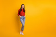 Full length body size photo of cute nice attractive millennial youngster with hands in pockets standing near empty space smiling toothily isolated over vivid color background