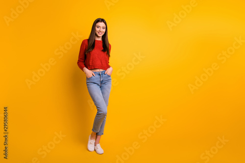 Obraz Full length body size photo of cute nice attractive millennial youngster with hands in pockets standing near empty space smiling toothily isolated over vivid color background - fototapety do salonu