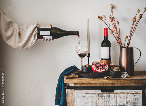 Red wine, board with cheese, fruit, almonds and olives, candles, decorative flowers on kitchen counter and womans hand pouring wine to glass, white wall at background Canvas Print